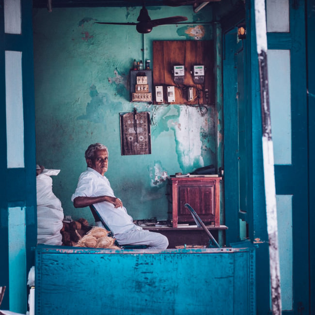 Indien. Ein Mann sitzt entspannt auf einem Stuhl.
