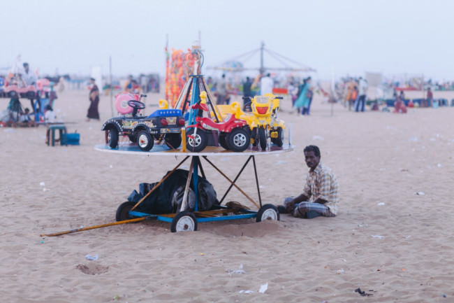 Indien. Ein Mann sitzt vor einen selbstgebauten Karussell.