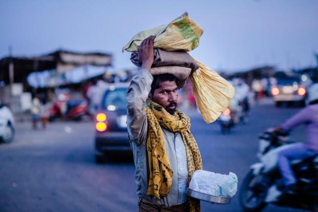 Indien. Ein Mann hält auf der Straße verschiedene Dinge in der Hand und auf dem Kopf.