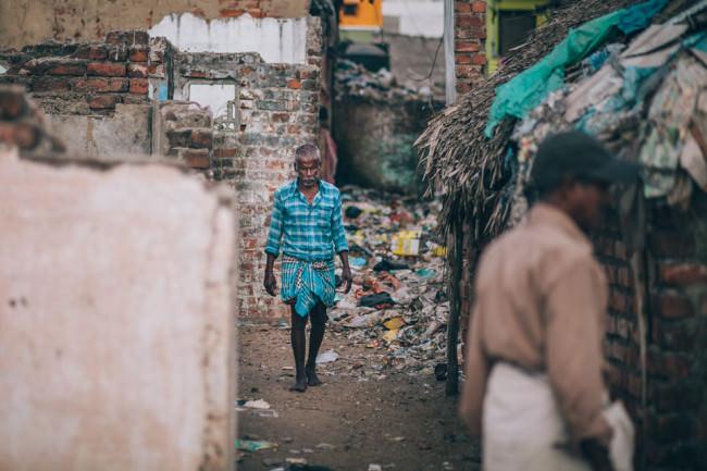 Indien. Ein Mann läuft durch eine müllbeladene Häuserreihe.