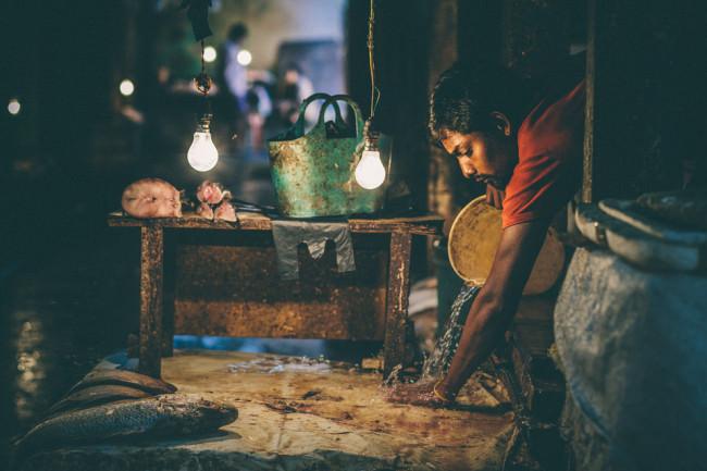 Indien. Ein Mann macht etwas mit Wasser und Sand.