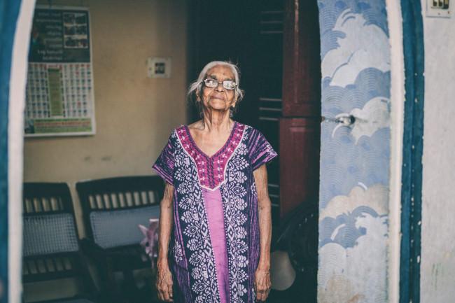 Indien. Eine ältere Frau mit Brille schaut in die Kamera.