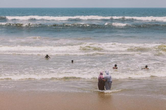 Indien. Zwei Frauen stehen am Strand und schauen Kindern beim Baden zu.