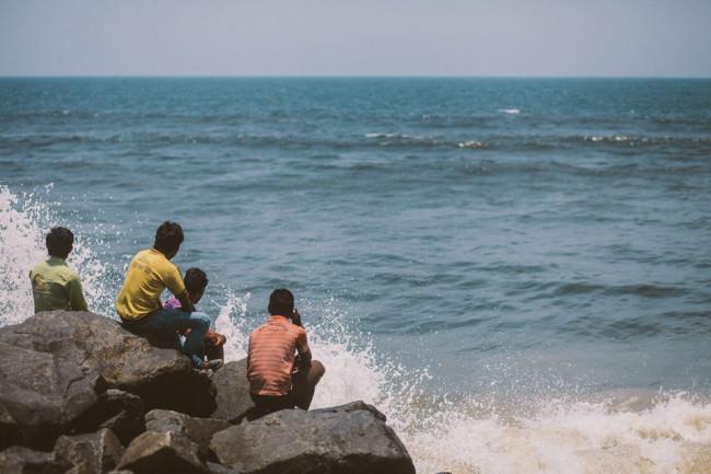Indien. Ein paar Männer sitzen auf Steinen und schauen aufs Meer.