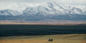 Zwei Reiter passieren die Steppe vor einem Gebirgsmassiv.