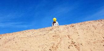 Hinter einer Sanddüne vor strahlend blauem Himmel steht eine Person, deren Gesicht ein gelber Smiley-Luftballon verdeckt.