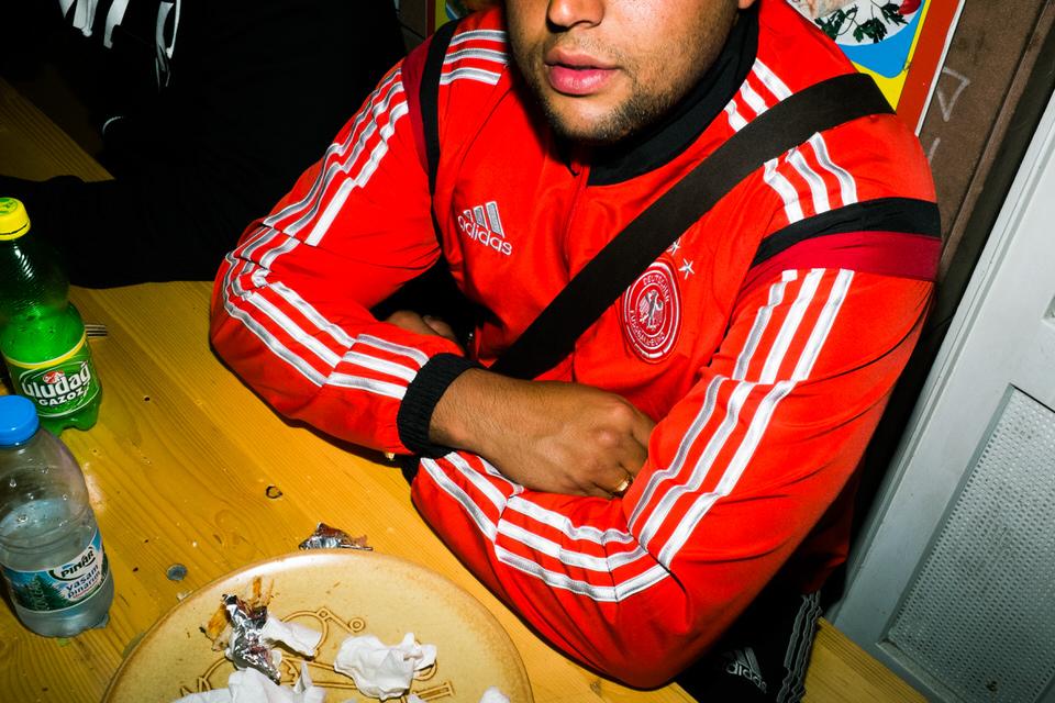 Straßenfotografie: Mann in rotem Adidas-Trainingsanzug nach dem Essen.