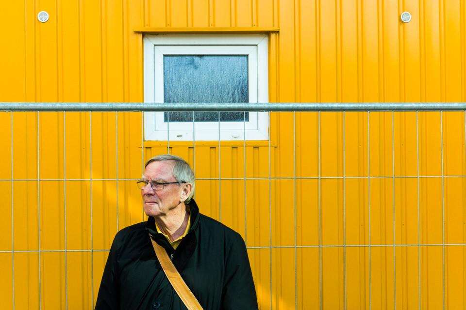 Straßenfotografie: Mann mit gelbem Gurt steht vor gelbem Baustellenhäusschen.