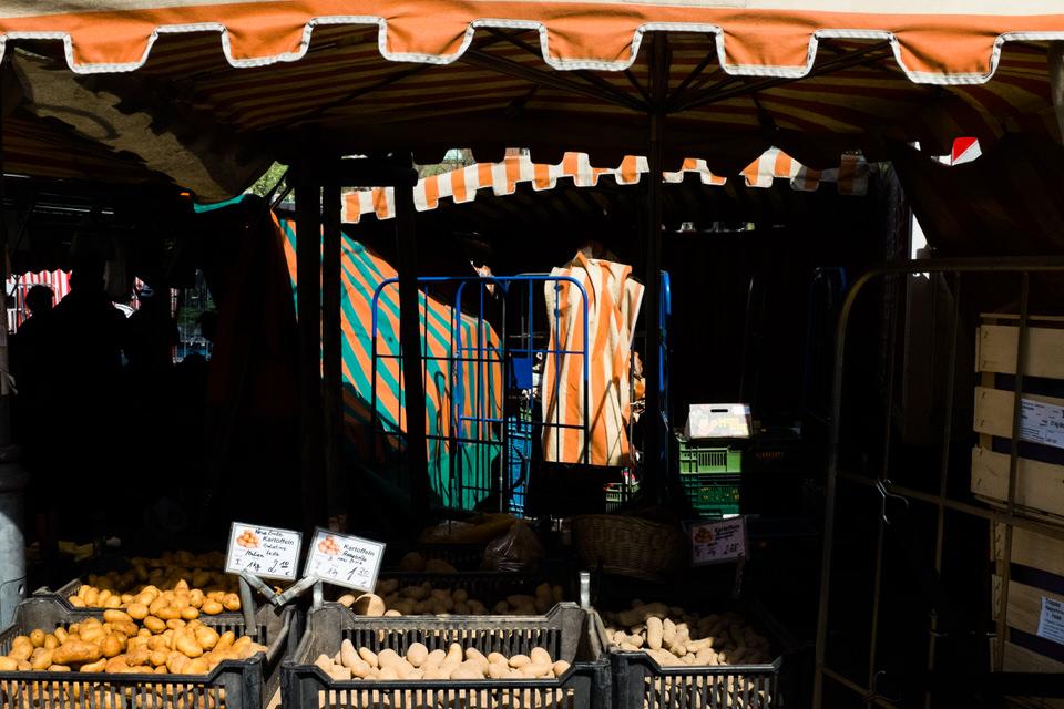 Straßenfotografie: Verschiedenfarbene Marktplanen in orange und weiß.