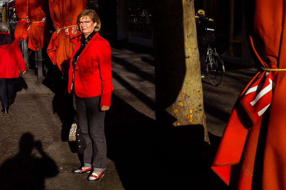 Straßenfotografie: Frau in roter Jacke vor roten Schirmen.