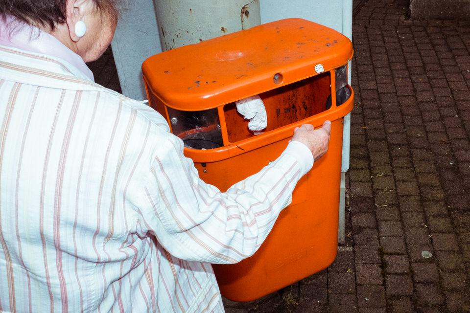 Straßenfotografie: Eine ältere Frau wirf ihr Taschentuch in einen orangen Mülleimer.