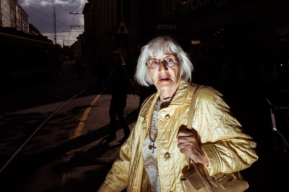 Straßenfotografie: Eine Frau in goldener Kleidung schaut zum Betrachter.