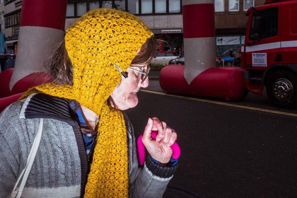 Straßenfotografie: Eine Frau mit gelbem Schal um den Kopf schaut zur Seite.