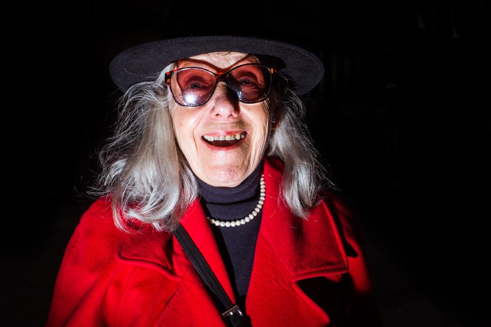 Straßenfotografie: Eine ältere Frau mit Hut und roter Jacke lacht in die Kamera.