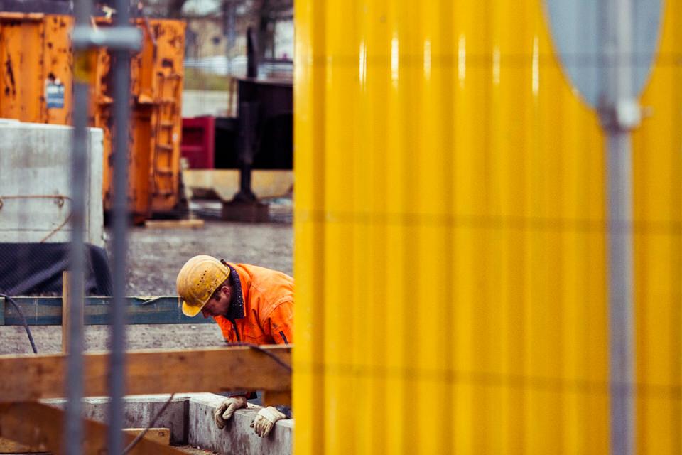 Straßenfotografie: Bauarbeiter hinter gelbem Baustellengehäus.