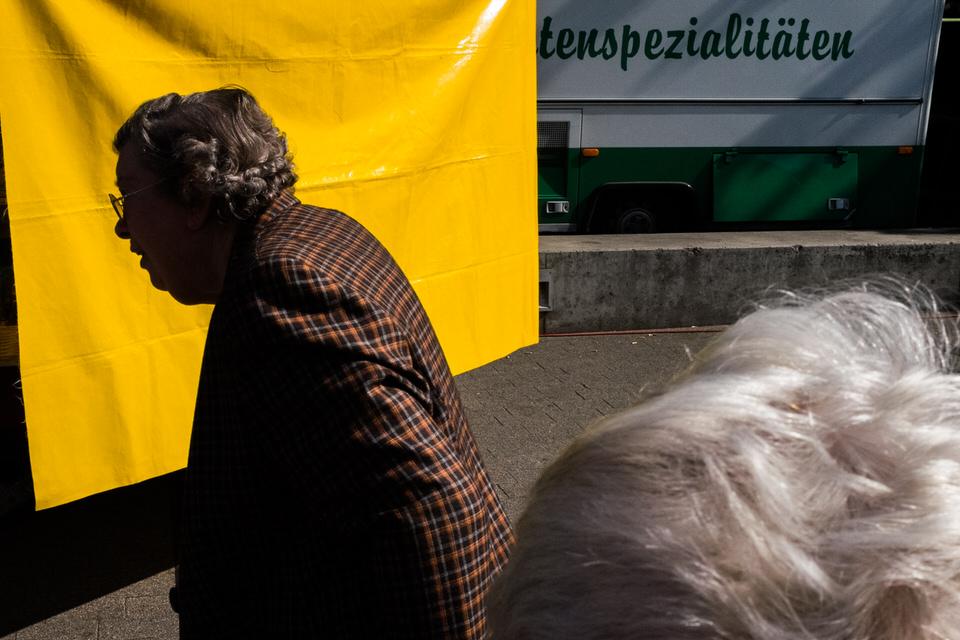 Straßenfotografie: Ein älterer Herr vor gelbem Hintergrund.