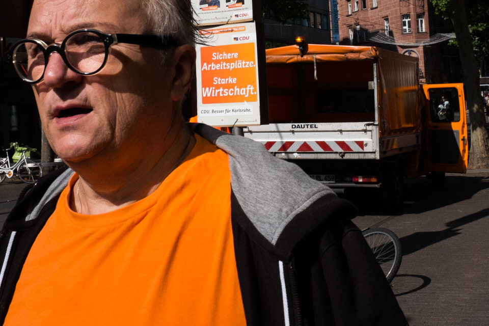 Straßenfotografie: Ein Mann in orangem T-Shirt vor vielen anderen orangen Dingen.