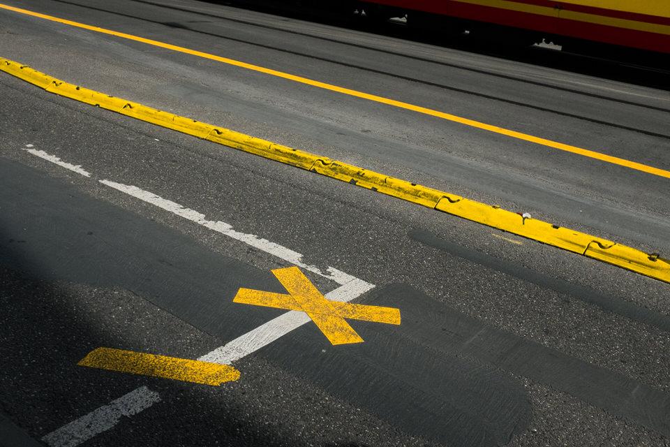 Straßenfotografie: Straßenmarkierungen in weiß und gelb.