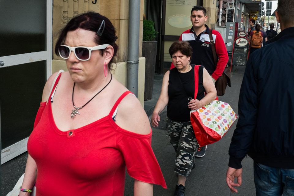 Straßenfotografie: Drei Personen in rot, weiß und schwarz.