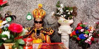 Ein Mann ist als König verkleidet, trägt Sonnenbrille und tippt in seinem Handy.