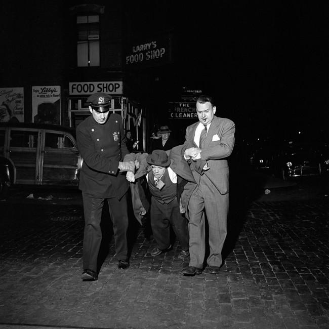 Eine Nachtaufnahme. Zwei Männer schleppen einen scheinbar Betrunkenen zwischen sich über die Straße.
