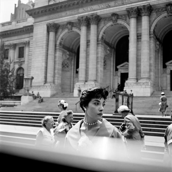 Eine schöne Frau steht im Mittelpunkt einer Straßenszene und sieht nach rechts.