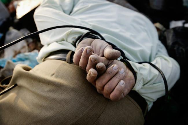 Die zusammengebundenen Hände eines auf dem Boden liegenden Mannes.
