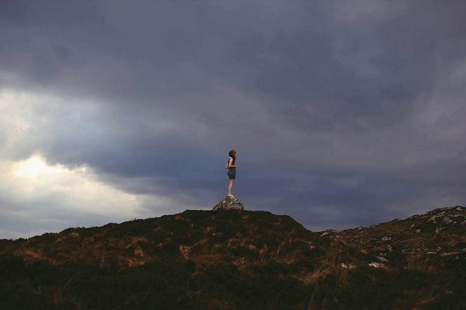 Ein Mädchen steht allein auf einem Berg und sieht in die Ferne.
