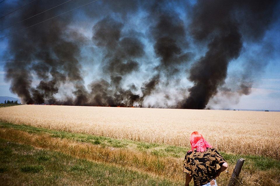 Eine Frau steht im Vordergrund und beobachtet dicke Rauschschwaden am Rande hinter einem Feld.