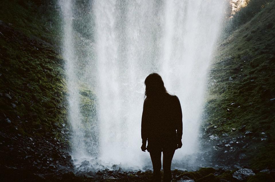 Eine Frau steht vor einem Wasserfall. Sie ist durch das Gegenlicht nur als Schatten zu erkennen.