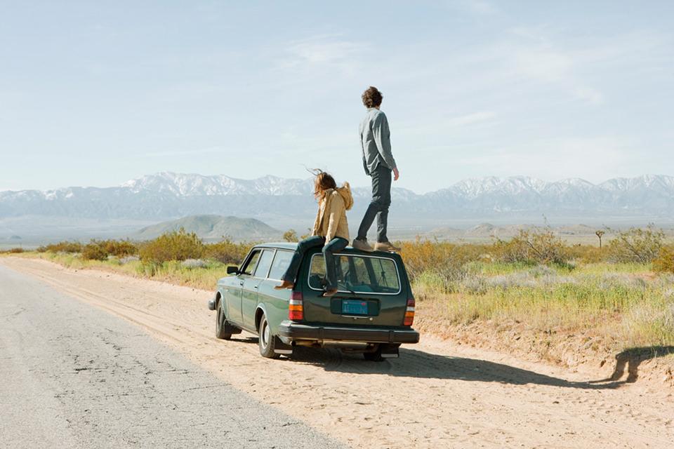 Zwei Menschen stehen auf einem Auto und sehen in die Ferne.