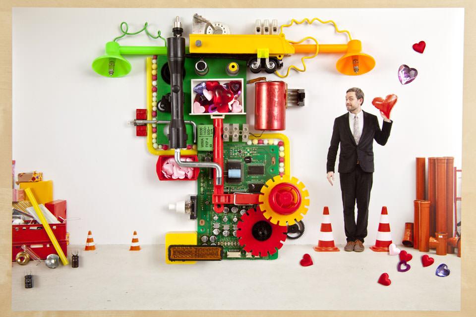 Eine Maschine. Rechts steht ein lächelnder Mann im Anzug mit Herzluftballon in der Hand.