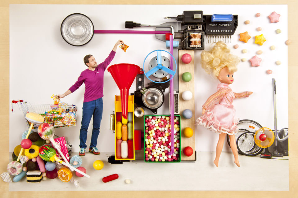 Auf der linken Seite der Maschine liegt jede Menge Süßes, auf der rechten Seite läuft eine Barbie gerade heraus.
