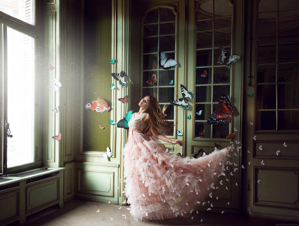 Eine Frau in einem Märchenkleid von Schmetterlingen umrahmt.