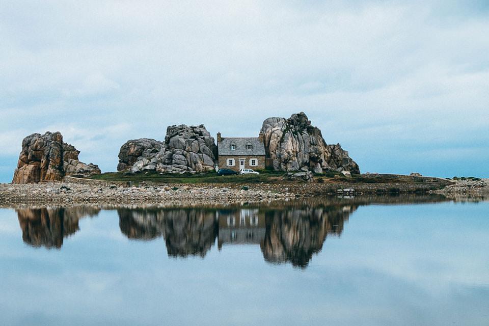 Ein Haus von Felsen umrahmt vor einem See.