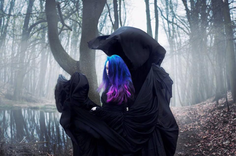 Eine Frau mit wehendem Gewand steht in einem nebligen Wald.