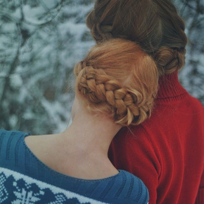 Zwei Mädchen mit hübschen, geflochten Zöpfen sind von hinten zu sehen.