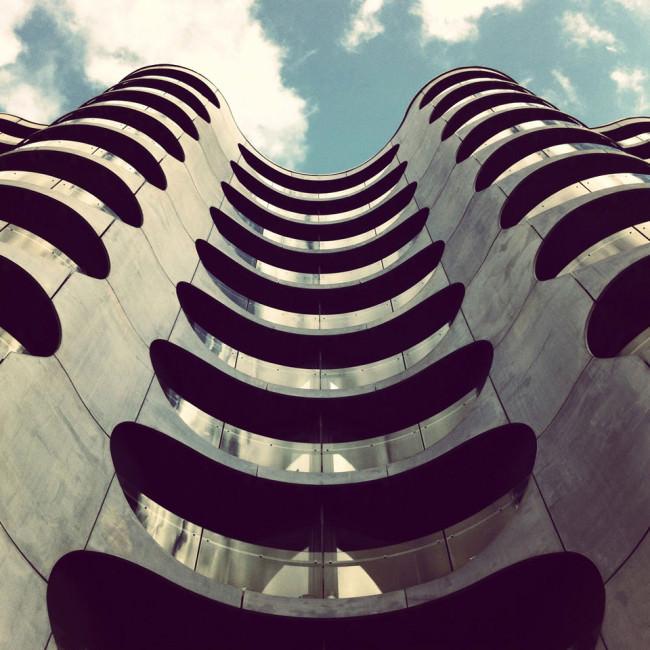 Blick hinauf an einer Fassade mit runden Öffnungen und Glasbrüstungen