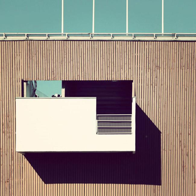 Balkon an einer vertikal mit Holz verkleideter Fassade
