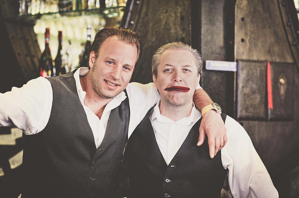 Zwei Kellner posieren für die Kamera.
