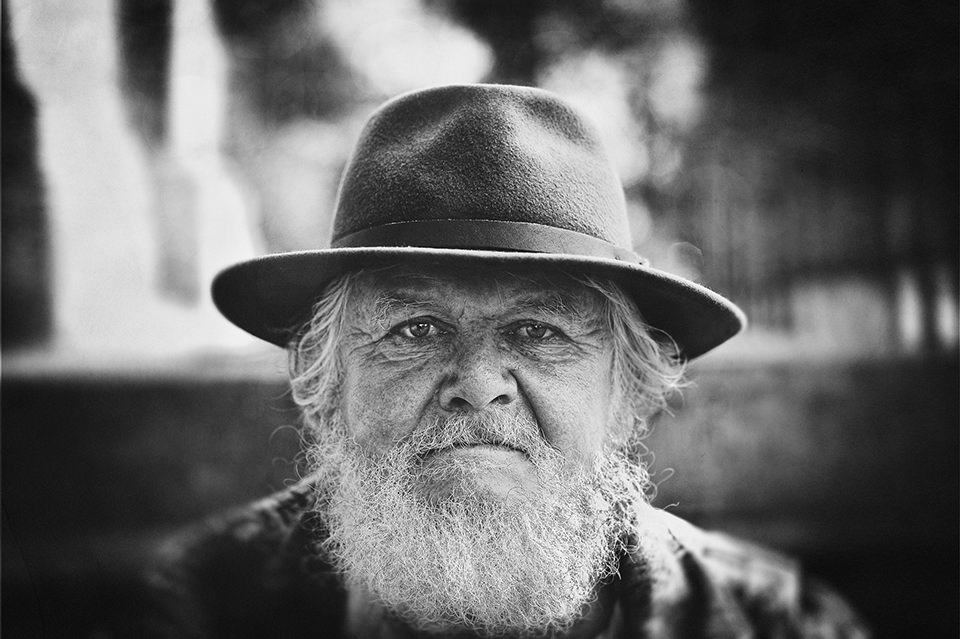 Alter Mann mit Bart und Hut sieht in die Kamera.