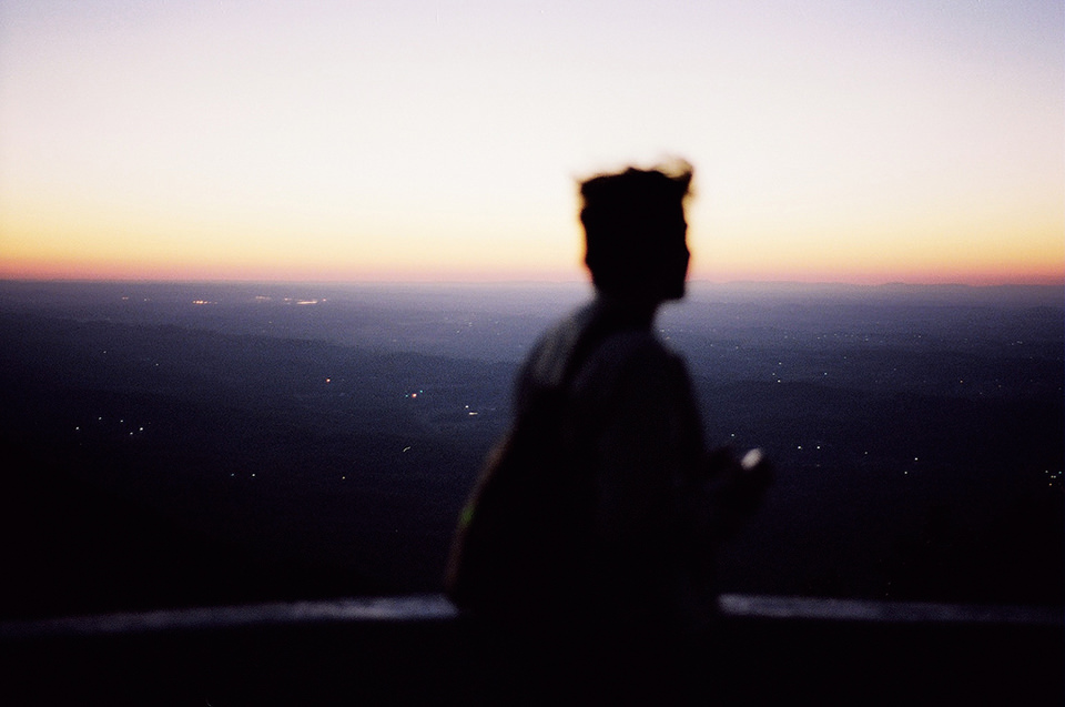 Ein Mann steht unscharf im Vordergrund. Im Hintergrund sieht man die Lichter einer Stadt.