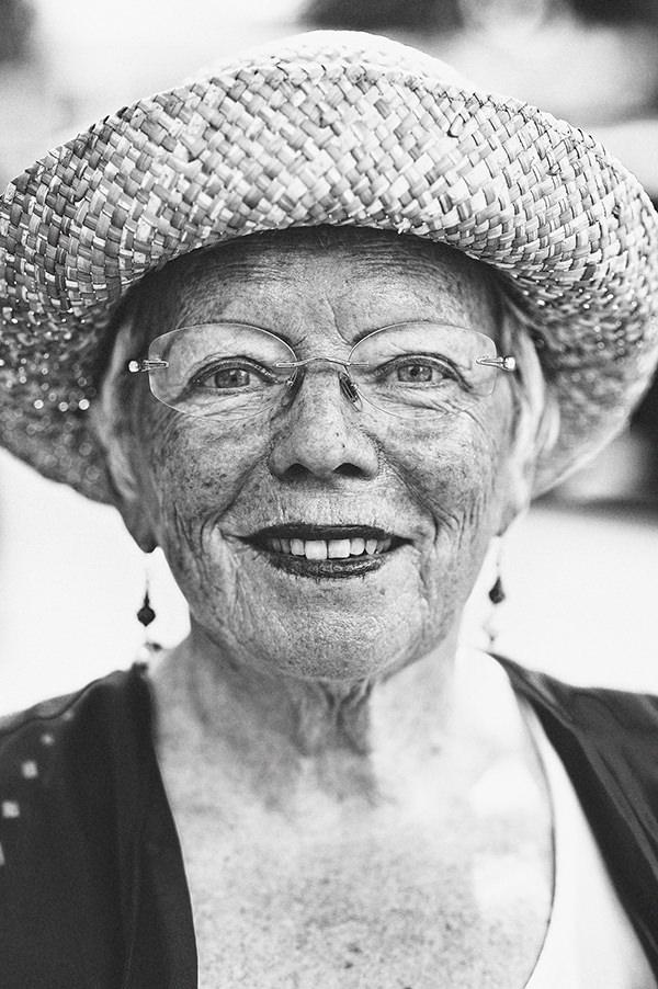 Frau mit Hut lächelt in die Kamera.
