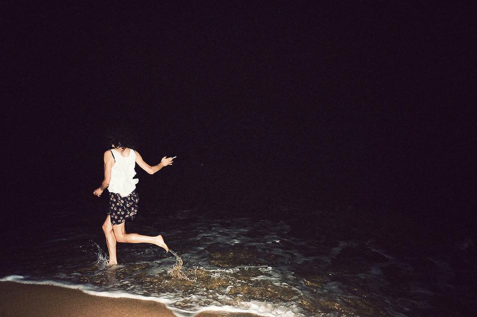Ein Mann mit Zigarette springt am Strand in die Wellen.
