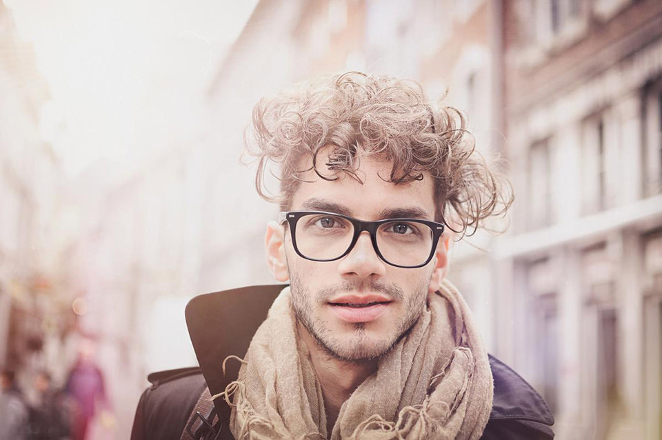 Junger Mann mit Locken und Brille lächelt in die Kamera.