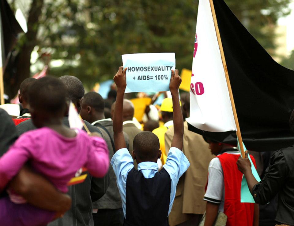 Eine Gruppe von Menschen steht mit dem Rücken zur Kamera. Ein Junge hält ein Blatt mit beiden Händen nach oben, darauf steht: Homosexuality +  AIDS = 100%