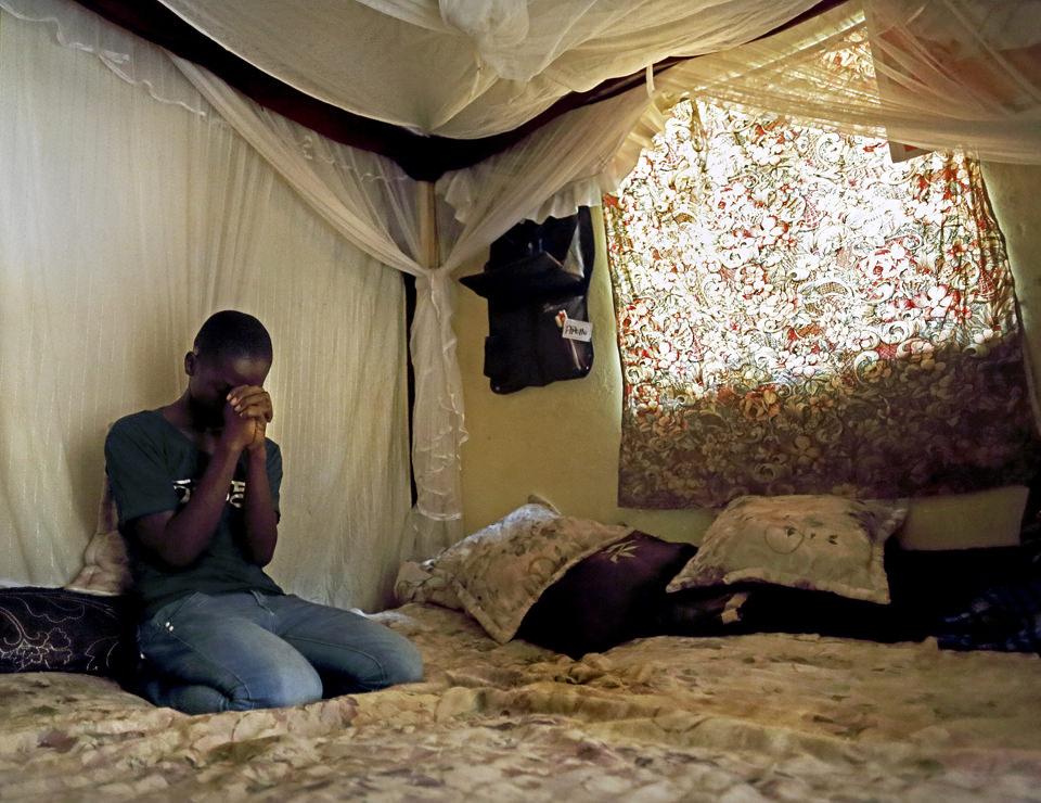 Ein Mann hockt auf einem Bett und betet.