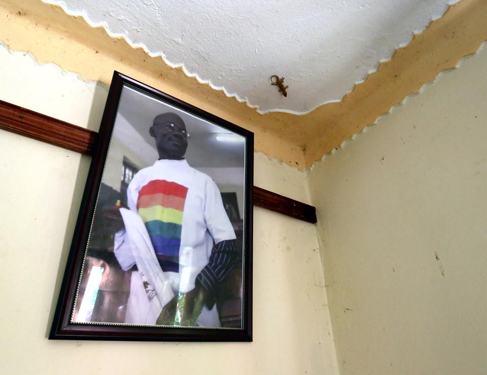 In einer Zimmerecke hängt ein Portrait von einem Mann mit Regenbogen-T-Shirt. An der Decke läuft ein Salamander.