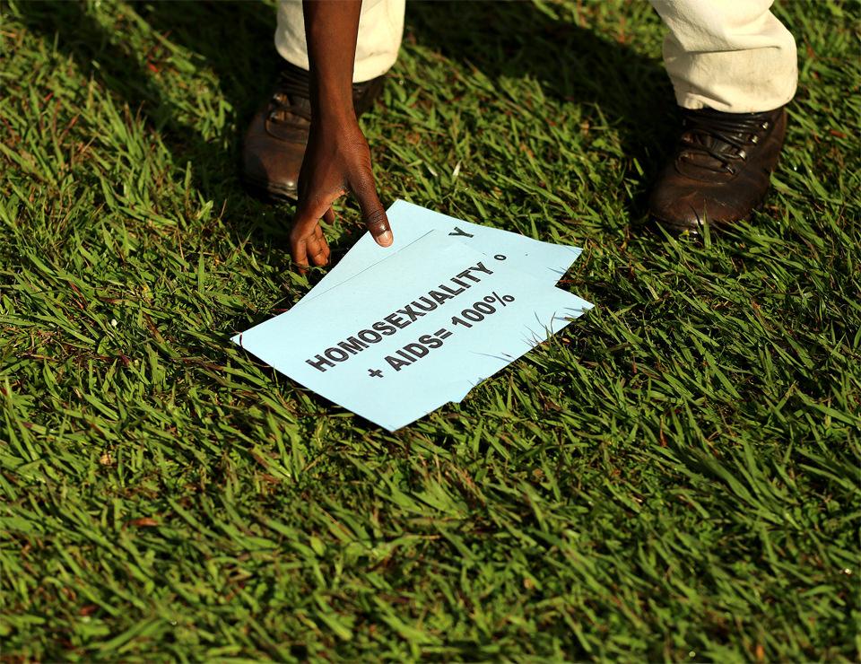 Jemand greift nach einem Blatt, das auf dem Boden liegt. Darauf steht: Homosexuality +  AIDS = 100%