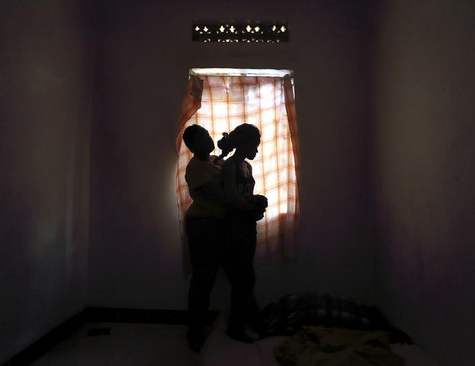 Zwei Frauen umarmen sich vor einem Fenster.